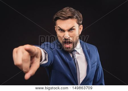 You. Irritated businessman is shouting at someone with aggression. He is standing and pointing finger forward. Isolated