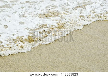 a gentle wave washing up on a beach causing white foam and bubbles