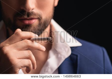 Close up of male smoker hand holding cigarette with enjoyment. Isolated