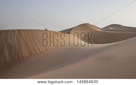 Man in traditional outfit in a desert at sunrise
