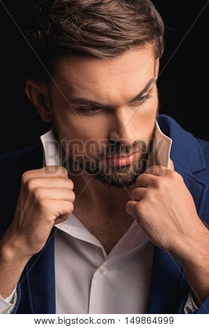 Confident young businessman is adjusting shirt collar and posing. He is standing and looking aside with seriousness. Isolated