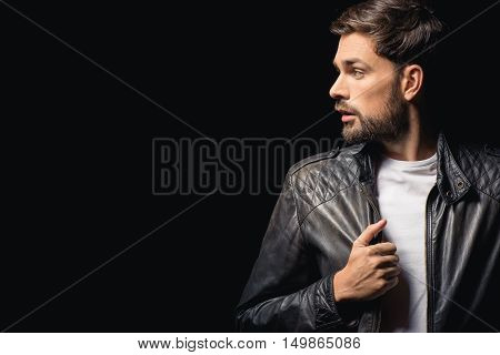 Young man is standing and looking aside with seriousness. He is touching his leather jacket. Isolated and copy space in left side