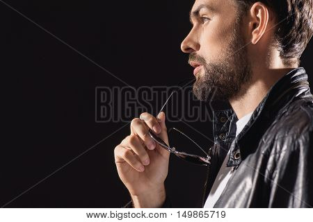 Pensive young man is standing and holding glasses near his mouth. He is looking forward with seriousness. Isolated and copy space in left side