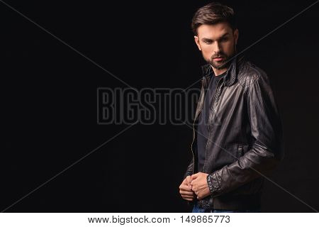 Serious young man is standing and looking forward pensively. He is wearing leather jacket. Isolated and copy space in left side