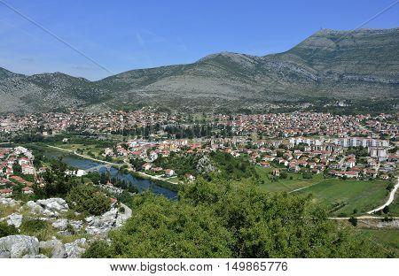 An aerial shot of the town of Trebinje in Bosnia taken from Crkvina Hill showing the historic 16th century Ottoman Arslanagica Most bridge over the Trebisnjica River.