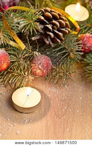 Beautiful Christmas card. Christmas fir-tree red ball golden ribbon and candles on wooden background