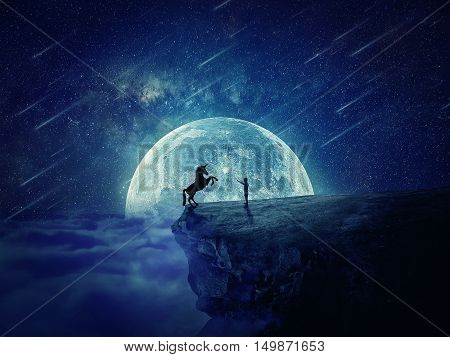 Night scene with a boy standing at the edge of a cliff chasm trying to tame a wild unicorn. Begining of a new friendship fearless symbol