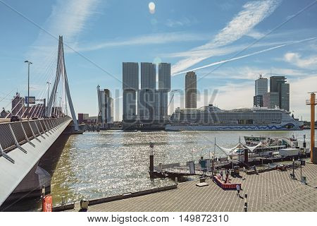 Rotterdam, Netherlands - May 26: Rotterdam, Netherlands - May 26, 2016: Picture of the Erasmus bridge and and for the building the Rotterdam along the Wilhelminakade has the AIDA cruise ship docked, taken August 18, 2016 in Rotterdam, Netherlands.
