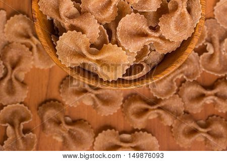 Wholegrain Farfalle into a bowl. wholemeal. Integral over a wooden table