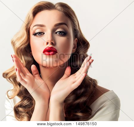 Beautiful woman  looks like a star of a retro movie . Vintage pin-up   girl  send air  kiss . Model with  curly hair and bright makeup with red lips. Hairstyle after salon and beauty face .