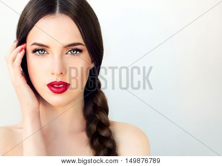 Beautiful  brunette model girl with  long braid hair . Hairstyle  pigtail  . Red lips and nails manicure . poster