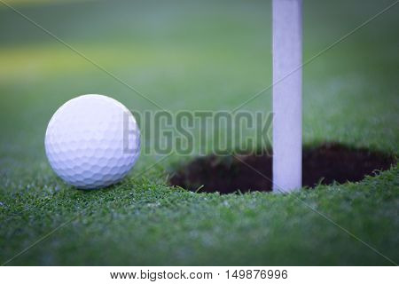 Golf ball near the hole, on the green next to the flag on the golf course.
