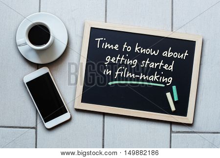 Chalkboard or Blackboard concept saying Time to know about getting started in filmmaking with coffee and mobile phone. Concept of filmmaking video blog education.