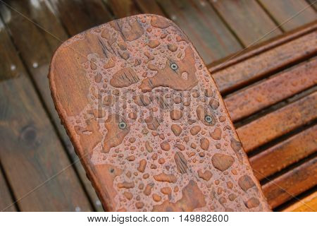 Rain droplets on an arm of a wooden chair on a deck outside
