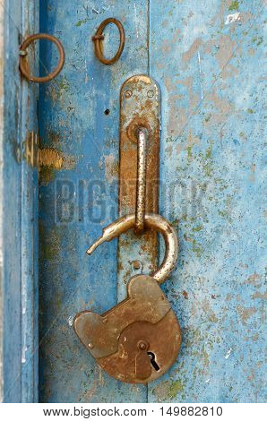an old wood blue painted door with metal rusted latch padlock and antique door handle.Vintage lock