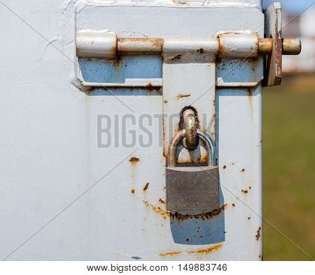 Partly rusted closed padlock in scratched metal latch with blurred background on right.