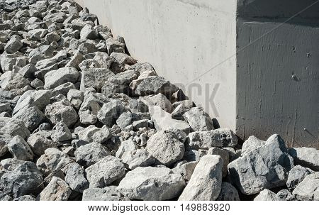 Uneven rock and gravel rubble by smooth gray concrete wall corner.