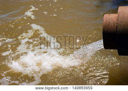 Water flowing from rusted metal culvert drain pipe opening and splashing into foamy brown water.