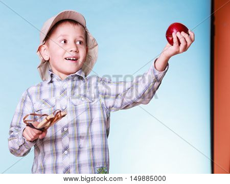 Nature and free time prankster little boy. Child have fun with wooden sling shot and fruit hold apple.