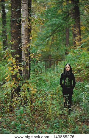 portrait of a cute pensive girl with a fern leaf on a black sweater in the thickets of the forest in the fall.