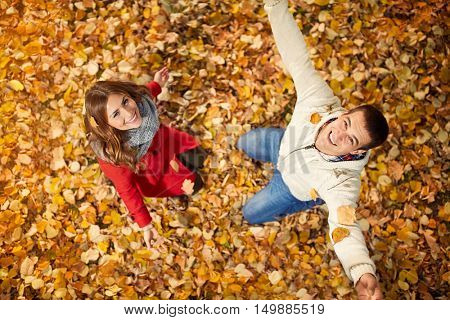 Cheerful girlfriend with partner enjoying in park on fallen leaves in autumn