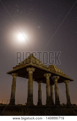 The royal cenotaphs of historic rulers, also known as Jaisalmer Chhatris, at Bada Bagh in Jaisalmer, Rajasthan, India. Night shot of ruins with a moon