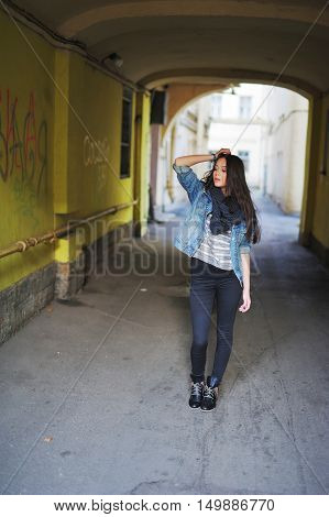 Attractive long-haired girl in a denim jacket and boots standing under the arch in the old courtyard in the center of St. Petersburg