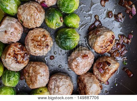 tasty juicy meatballs with brussels sprouts and fried onion on black teflon surface