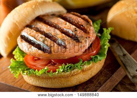 A delicious homemade grilled salmon burger with tomato and lettuce on a bun.