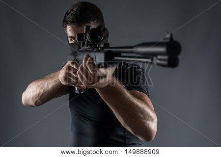 man in black military uniform aiming with rifle isolated on gray close-up