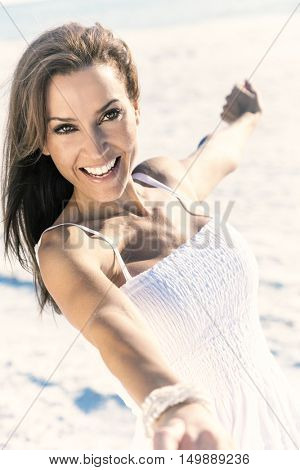 An attractive middle aged woman with perfect teeth dancing having fun in the sunshine on a beautiful tropical beach