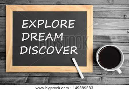 The words Explore Dream Discover on small chalkboard