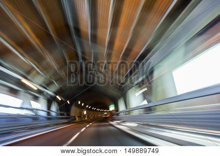 Motion blur driving a car at speed through a road tunnel
