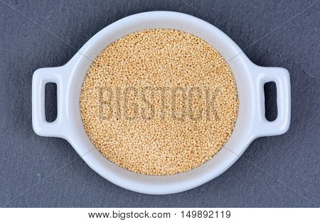 Amaranth seeds in a ceramic bowl on slate