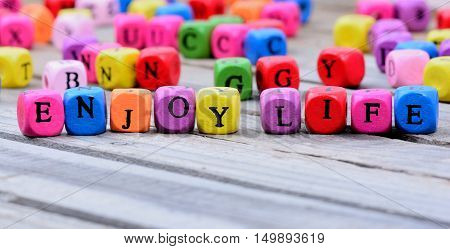 Enjoy life words on gray wooden table