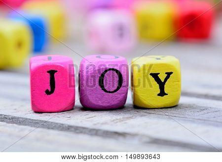 Joy word on gray wooden table closeup