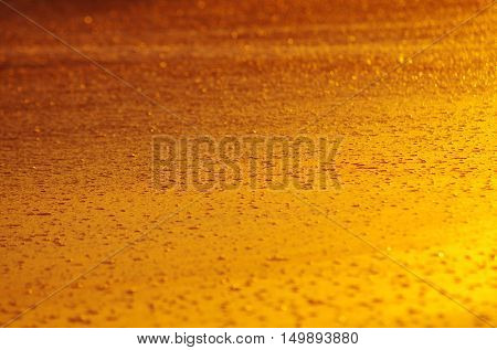 Golden background of wet sand in a beach under warm sunset light