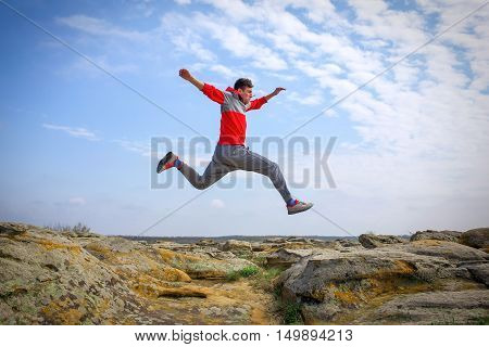 Sportsman running jumping over rocks in mountain area.