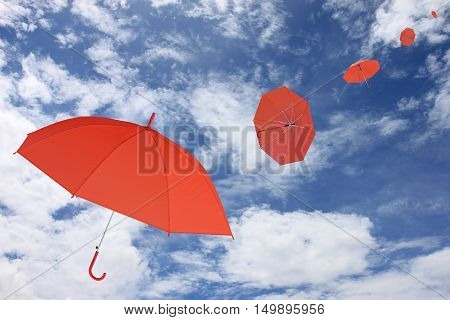 Red umbrella blown by the wind in concept for management business idea on blue sky and cloud background.