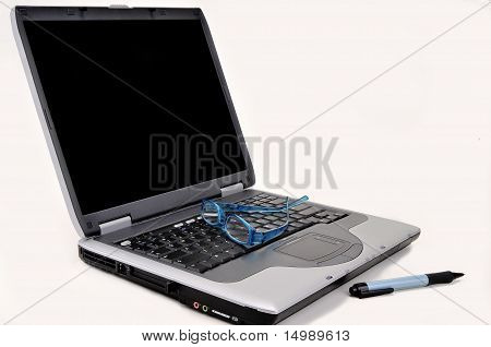 Laptop with glasses and pen