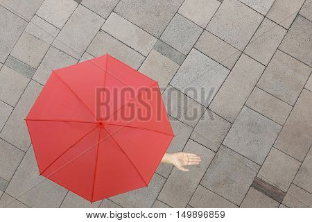 Red umbrella and a hand of man standing on stone floor and hand protruding outside the radius to determine whether it rains or notconcept of risks in business.