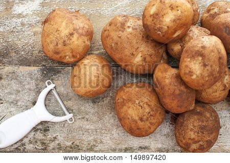 Pile of farm fresh potatoes still with adhering dirt and a manual peeler lying on a rustic background ready to prepare for dinner