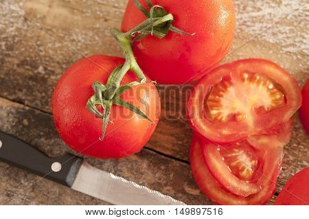 Sliced and whole fresh juicy ripe red tomatoes on the vine viewed from above on a rustic wooden table with a kitchen knife alongside
