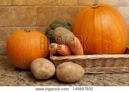 Harvest of fresh fall or autumn vegetables in a shallow wicker basket on a granite counter including carrots potatoes broccoli and pumpkins