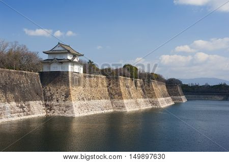 Exterior walls of the Osaka-jo castle Japan with a small pagoda overlooking the calm water of the surrounding moat a popular tourist attraction and museum