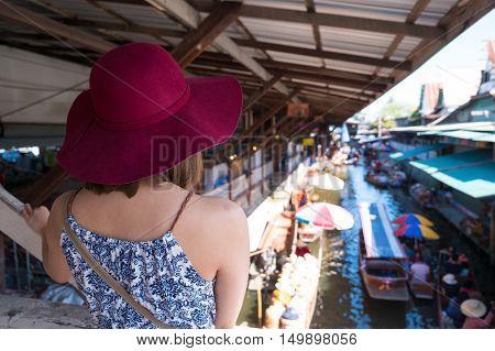 Young woman travel in Damnoen Saduak floating market in Ratchaburi province closed to Bangkok, Thailand.