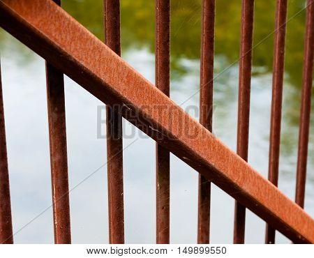 Large rusted metal beam diagonally across smaller vertical metal bars.