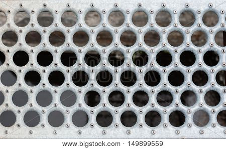 Gray metal grate with round holes and rivets against blurred background.