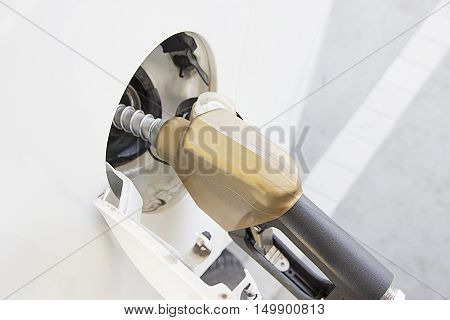 White car at gas station / Refueling hose. Petrol filling station