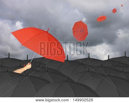 Red umbrella in hand and Surrounded by a black umbrellaumbrella other blown by windconcept for management business idea on rain cloud background.